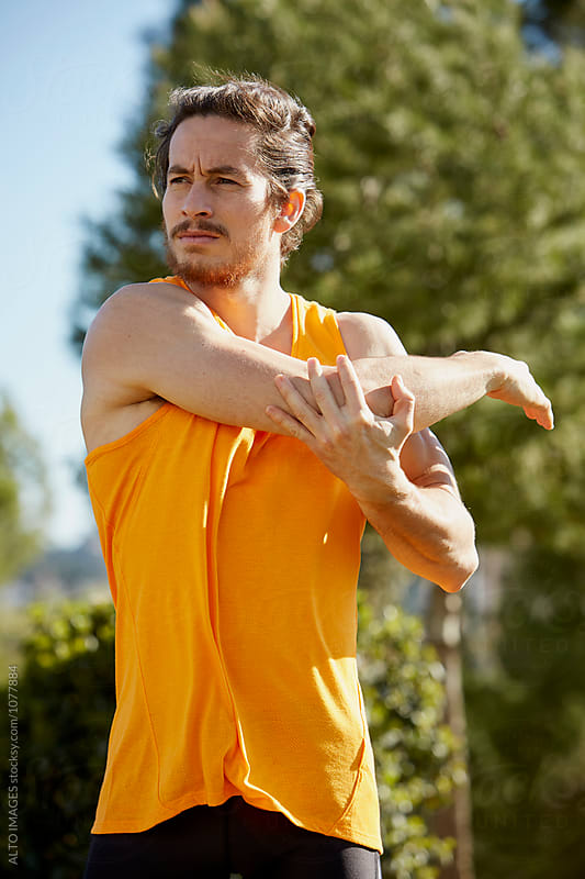 Fit Man Stretching Before Jogging In Park by ALTO IMAGES for Stocksy United