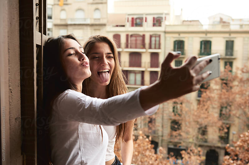 Young girlfriends maing faces while taking selfie by Guille Faingold for Stocksy United