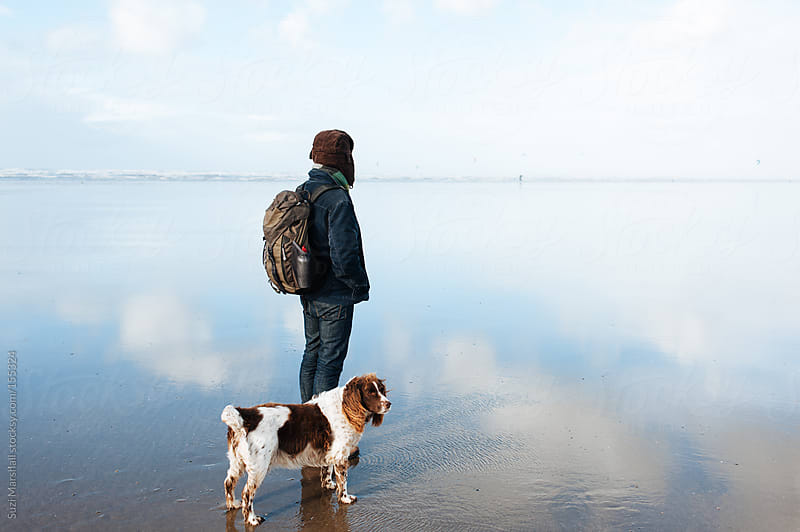 Man with his dog at the beach by Suzi Marshall for Stocksy United
