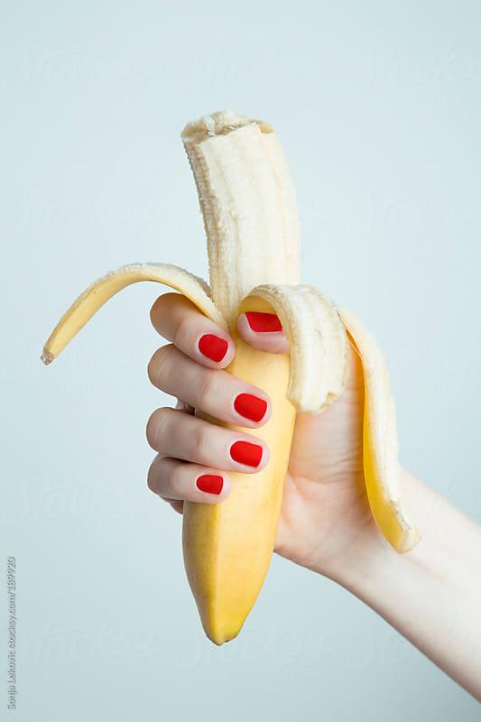 female hand holding a peeled biten banana by Sonja Lekovic for Stocksy United