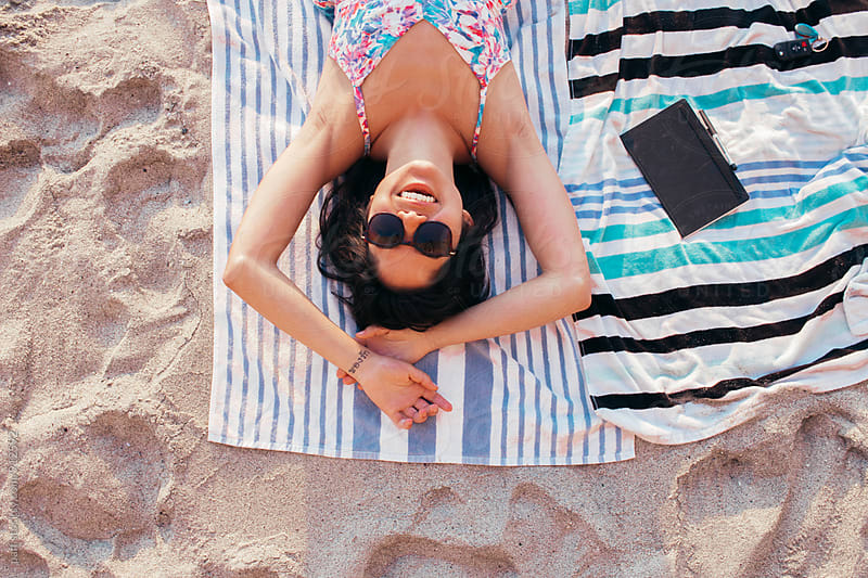 Girl smiling and lying on a towel at the beach in the summertime by paff for Stocksy United