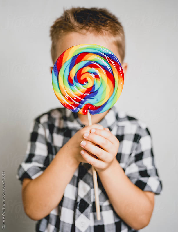 Young Boy Hiding Behind A Giant Lollipop by Cameron Whitman for Stocksy United