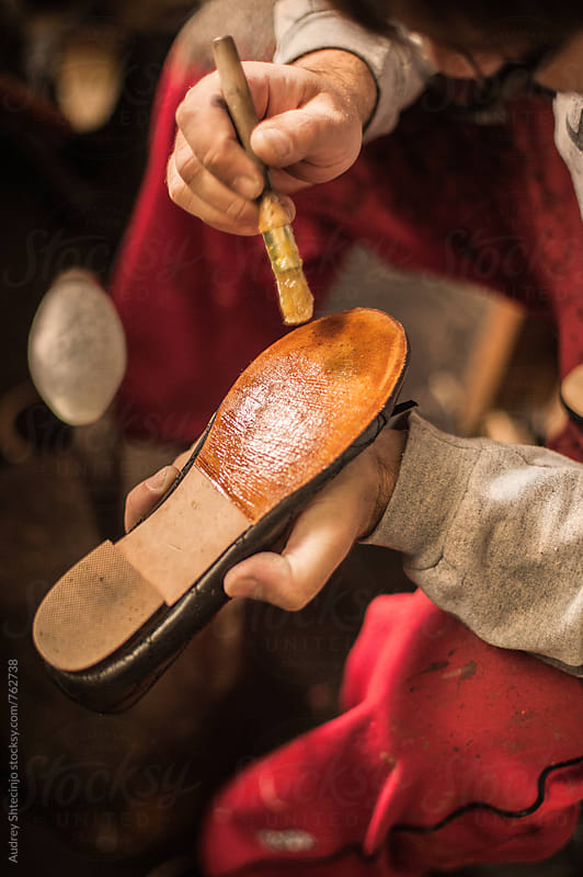 Close up/detail of shoemaker putting glue on shoes. by Audrey Shtecinjo for Stocksy United