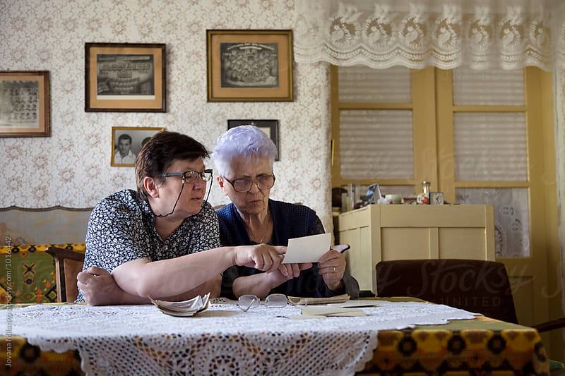 Adult woman and her senior mum looking trough the old family photos  by Jovana Milanko for Stocksy United