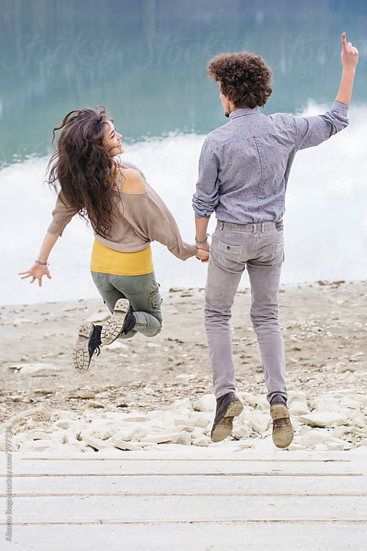 Back view of young couple jumping at the seashore. by Alberto Bogo for Stocksy United