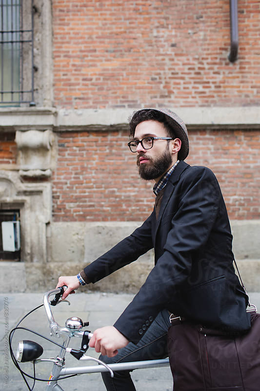 Young man wit beard riding his bicycle by michela ravasio for Stocksy United