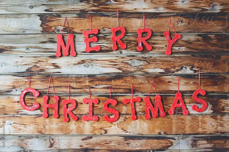 Wooden letters spelling Merry Christmas hang on a rustic wall by Tana Teel for Stocksy United