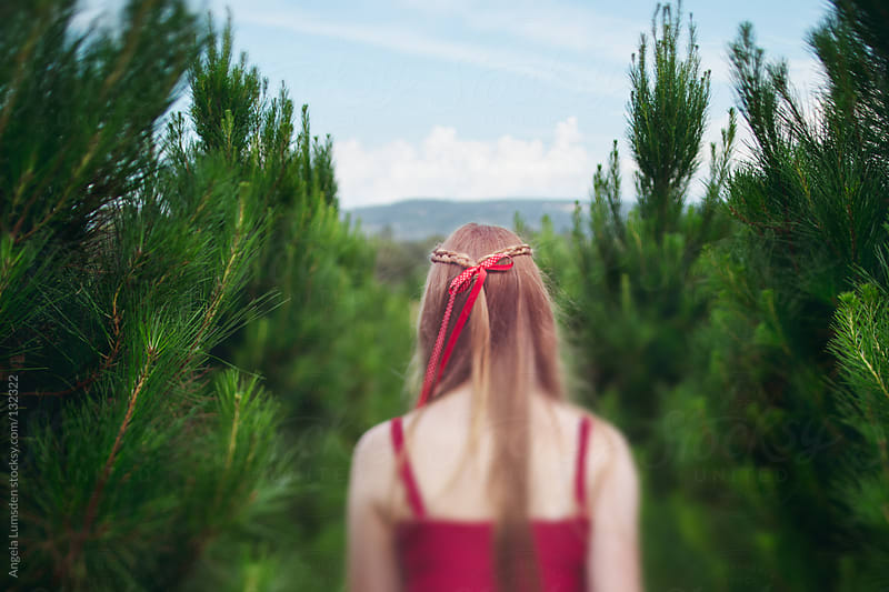 Teen girl in a row of christmas trees by Angela Lumsden for Stocksy United
