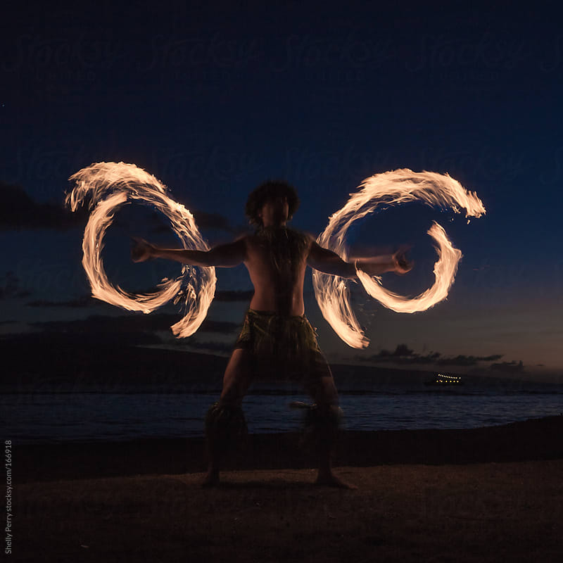 Traditional Hawaiian Fire Dancer spinning  his flames into wings. by Shelly Perry for Stocksy United