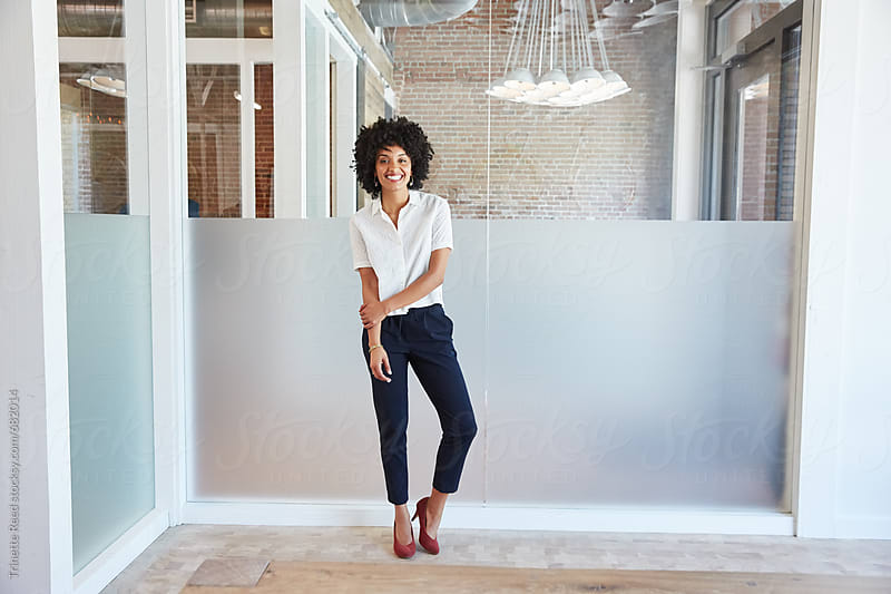 Portrait of strong and confident millennial businesswoman smiling by Trinette Reed for Stocksy United