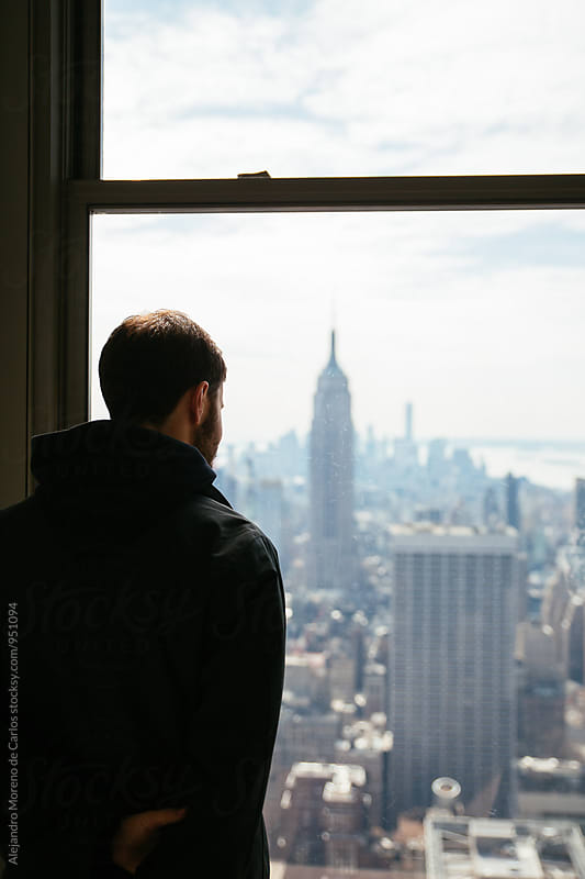 Bearded man enjoying New York through the window by Alejandro Moreno de Carlos for Stocksy United