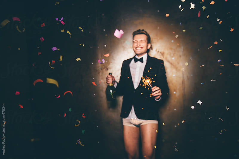 Men dressed in a suit and underpants with sparkler celebrating by Andrey Pavlov for Stocksy United