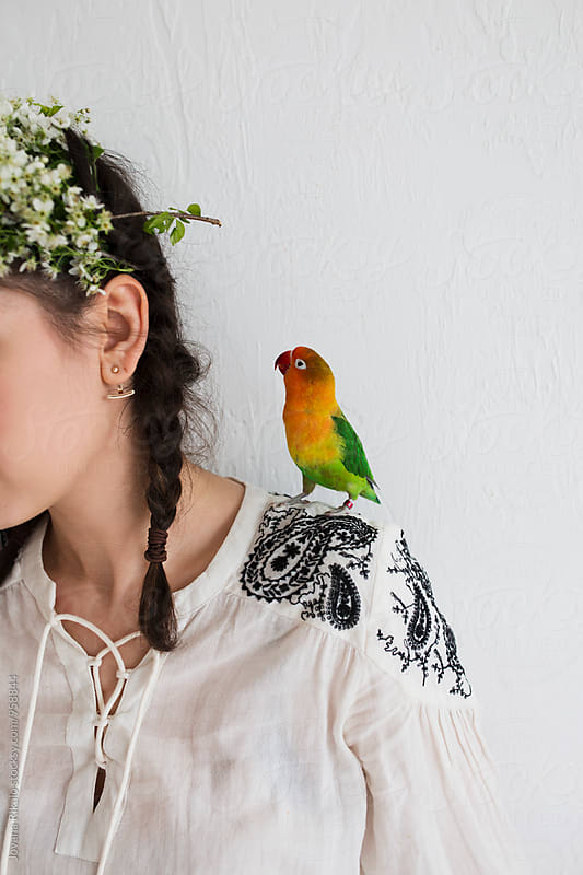 Cute parrot standing on woman's shoulder by Jovana Rikalo for Stocksy United