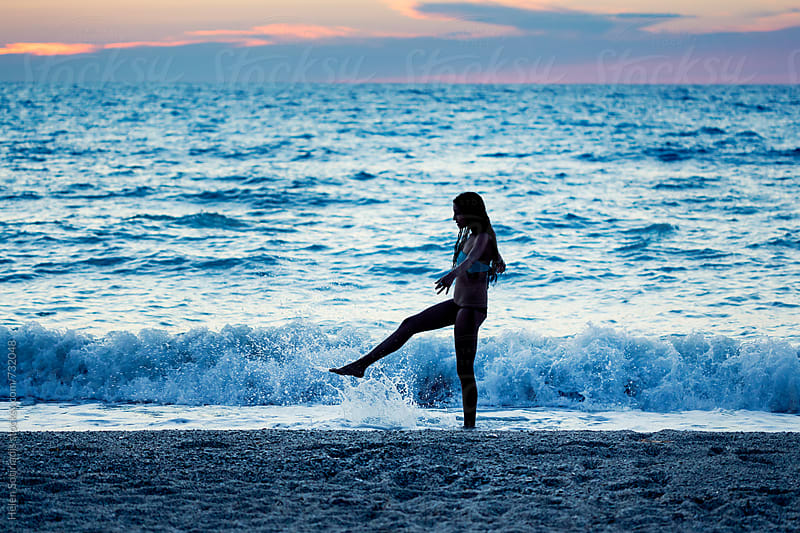 Young Woman Kicks the Water on the Beach at Twilight by Helen Sotiriadis for Stocksy United