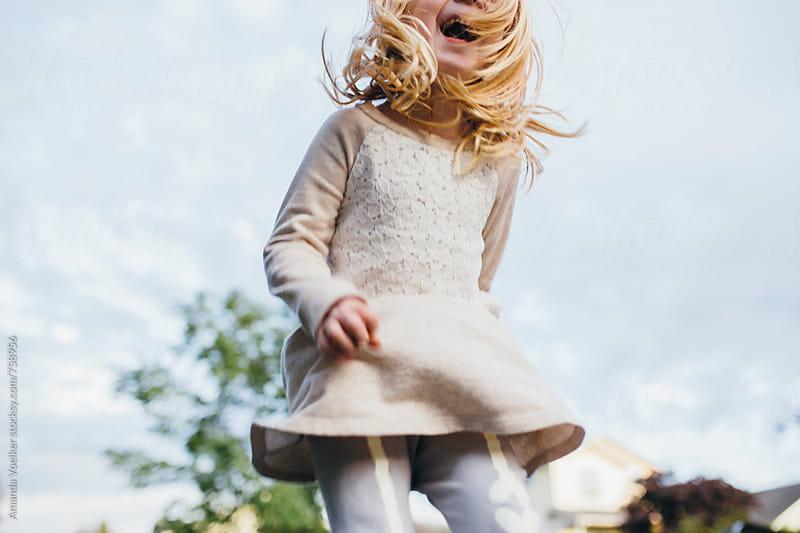 Crop Shot Of Little Girl Joyfully Jumping outside by Amanda Voelker for Stocksy United