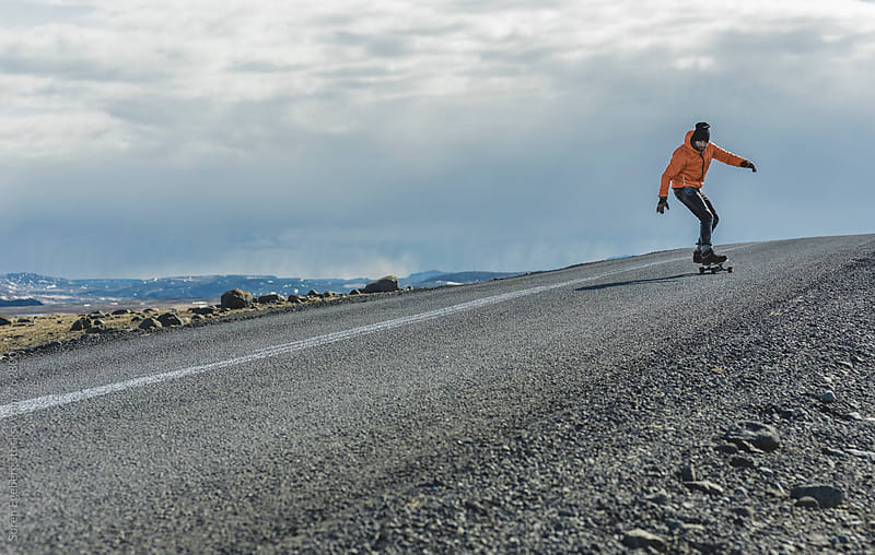 Man skateboarding on a road in Iceland road in Iceland by Søren Egeberg Photography for Stocksy United