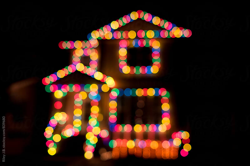 A house decorated with Christmas lights at night by Riley Joseph for Stocksy United