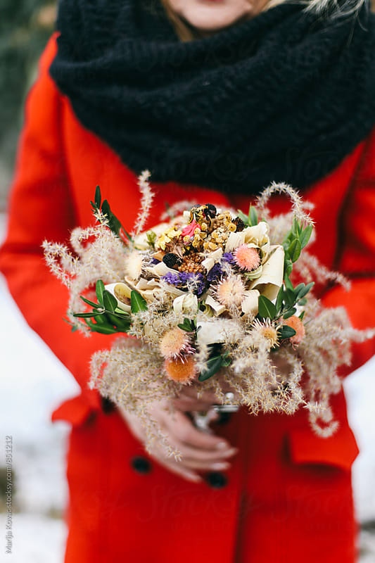 Woman in a red coat holding a bouquet of flowers  by Marija Kovac for Stocksy United