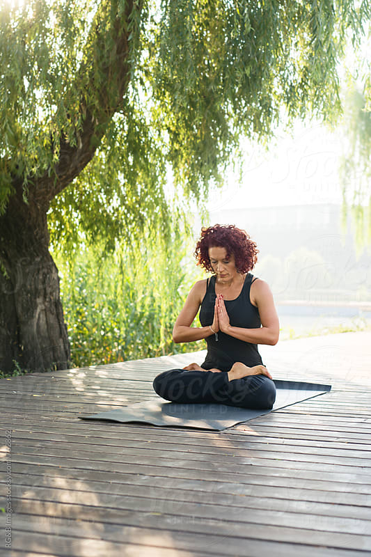 Woman meditating on a wooden deck outdoor by RG&B Images for Stocksy United