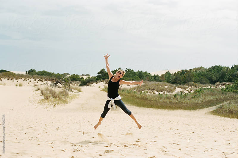 Happy woman jumping on a beach by Jakob for Stocksy United