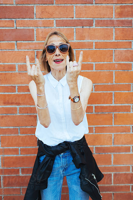 Senior woman doing the rock 'n' roll sign in front of a brick wall. by BONNINSTUDIO for Stocksy United