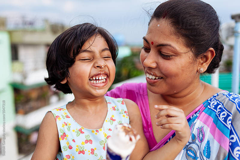 Mother and daughter enjoying an ice cream on a hot day by Saptak Ganguly for Stocksy United