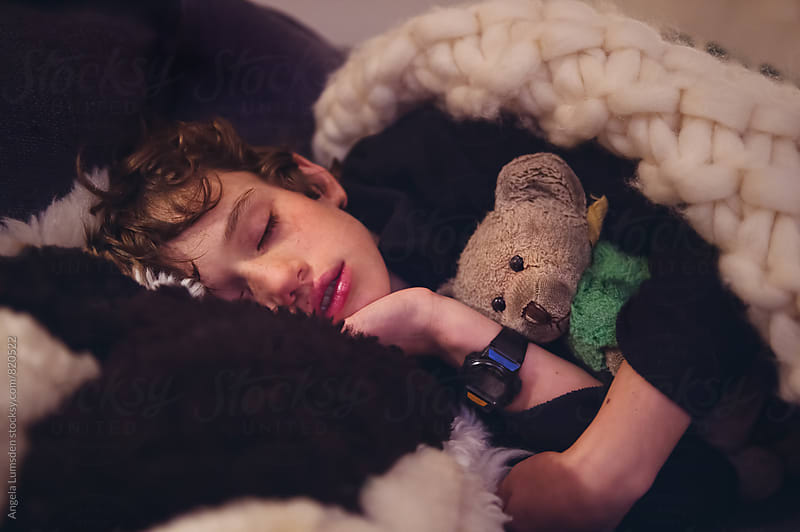 Close up of a sleeping boy and his teddy bear by Angela Lumsden for Stocksy United