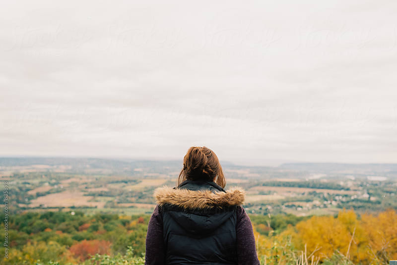 Woman standing before an overlook on a steel grey day in autumn by Joey Pasco for Stocksy United