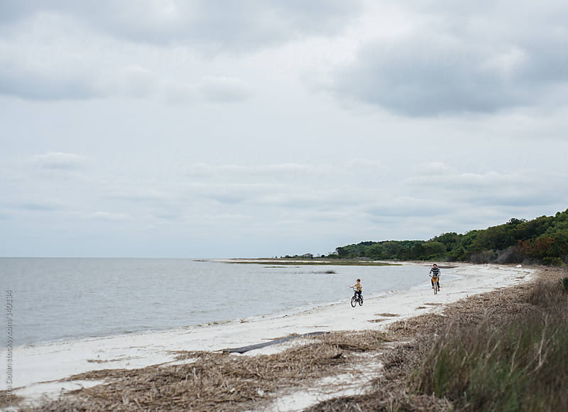 Father and son ride bikes together on a beach by Cara Dolan for Stocksy United