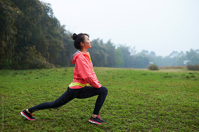 young asian woman doing warm up outdoor before running by Bo Bo for Stocksy United