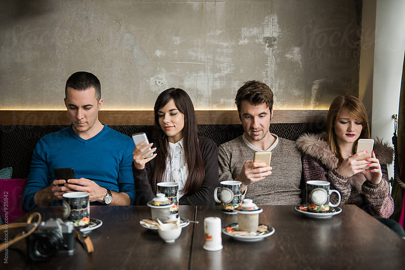 Four Friends Looking at their Mobile Phone in a Cafe by Mosuno for Stocksy United