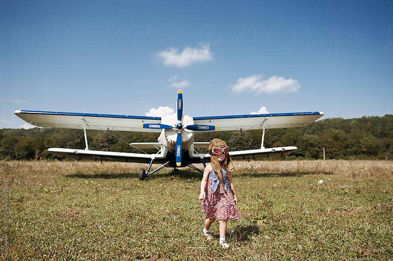 Little girl and propeller biplane airplane by Svetlana Shchemeleva for Stocksy United