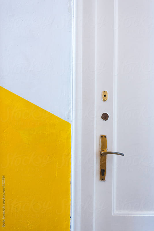 White door with yellow wall by Boris Jovanovic for Stocksy United