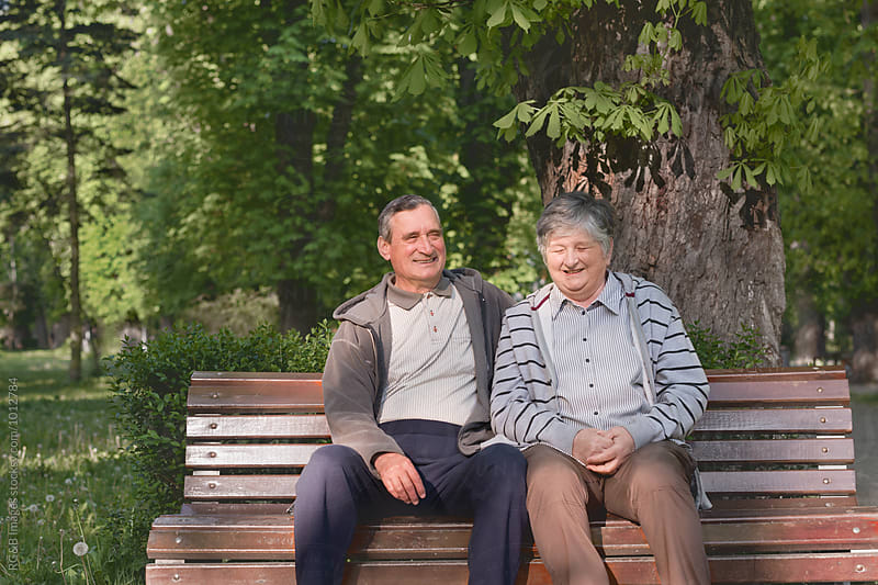 Elderly couple laughing on a bench in the park by RG&B Images for Stocksy United