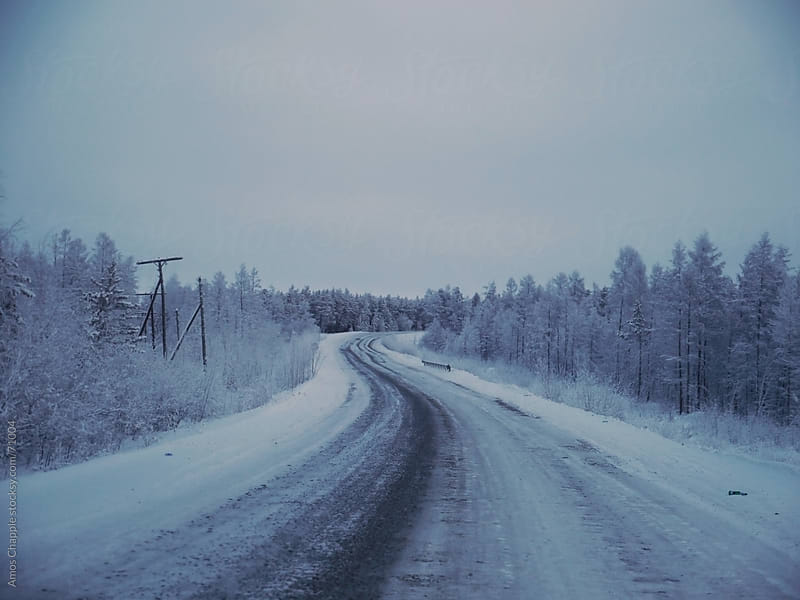 Winding Siberian road in winter.  by Amos Chapple for Stocksy United