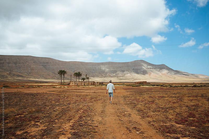Man walking through a desert landscape by Susana Ramírez for Stocksy United