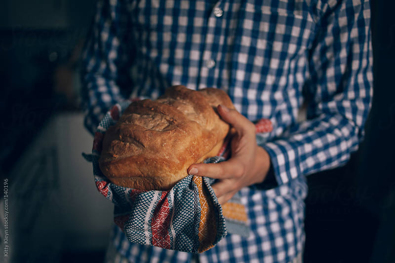 Man holding freshly baked bread by Kitty Kleyn for Stocksy United