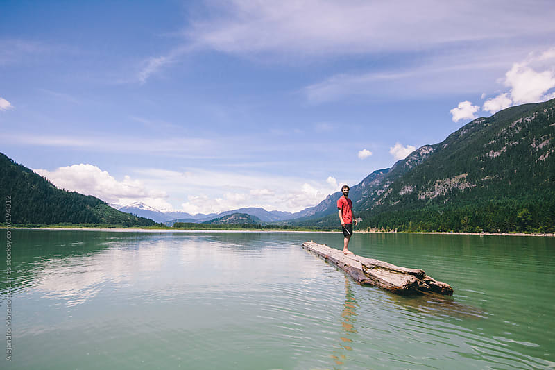 Young man standing on a floating log in a lake by Alejandro Moreno de Carlos for Stocksy United