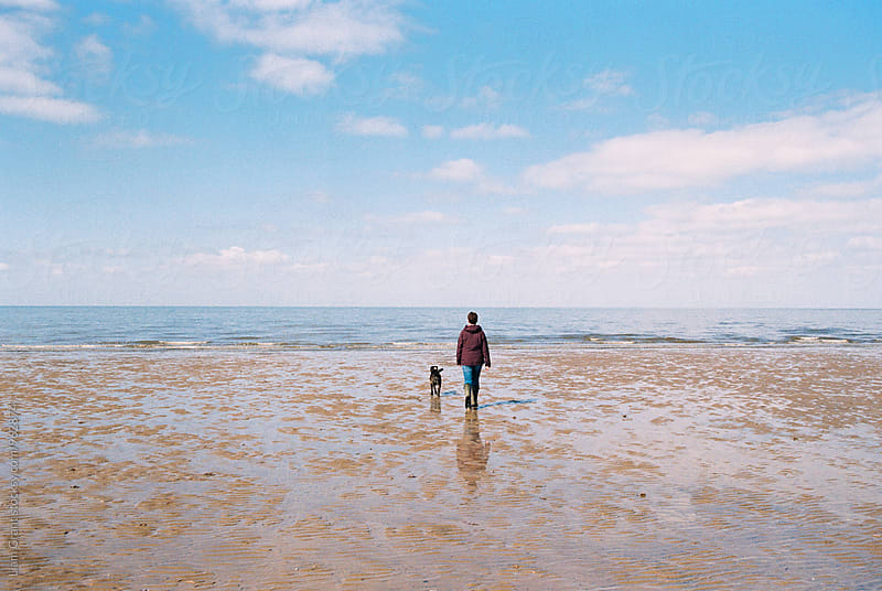 Female walking her dog on the beach at Old Hunstanton, Norfolk, UK. by Liam Grant for Stocksy United