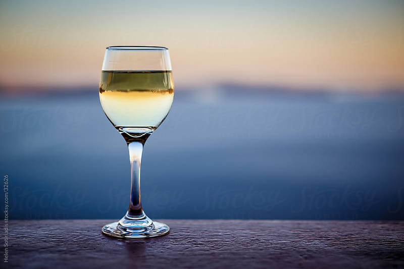 a glass of white wine by the sea by Helen Sotiriadis for Stocksy United