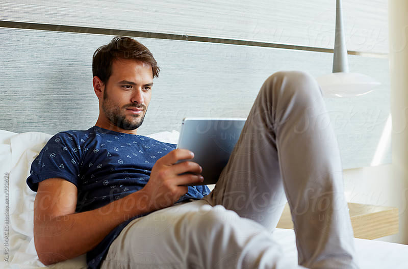 Man Using Digital Tablet On Bed In Hotel Room by ALTO IMAGES for Stocksy United