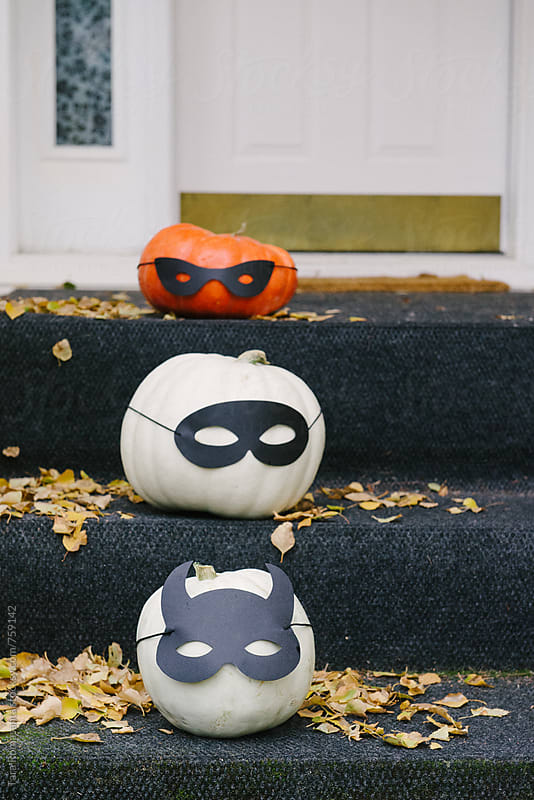 three pumpkins sitting on front stoop, decorated with masks by Tara Romasanta for Stocksy United