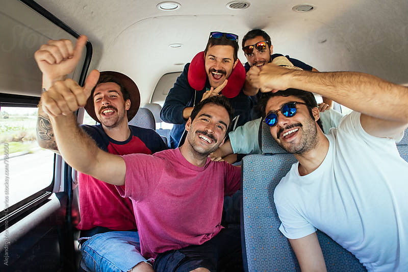 Group of young excited hipster men inside a van during a road trip by Alejandro Moreno de Carlos for Stocksy United