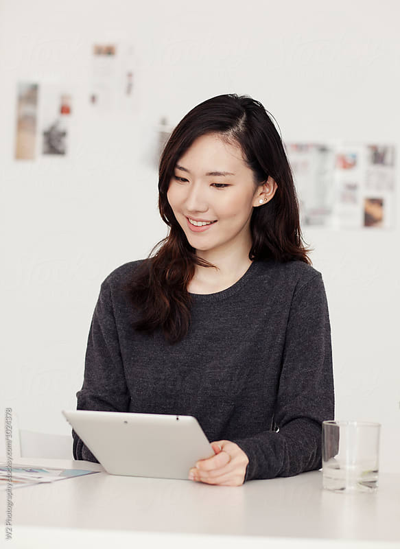 Young woman using a tablet pc at her desk. by W2 Photography for Stocksy United
