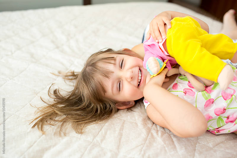 Happy little girl lying on the bed by michela ravasio for Stocksy United