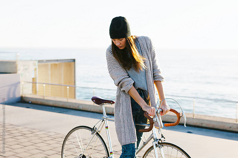 Woman standing with her vintage bicycle in the city. by BONNINSTUDIO for Stocksy United