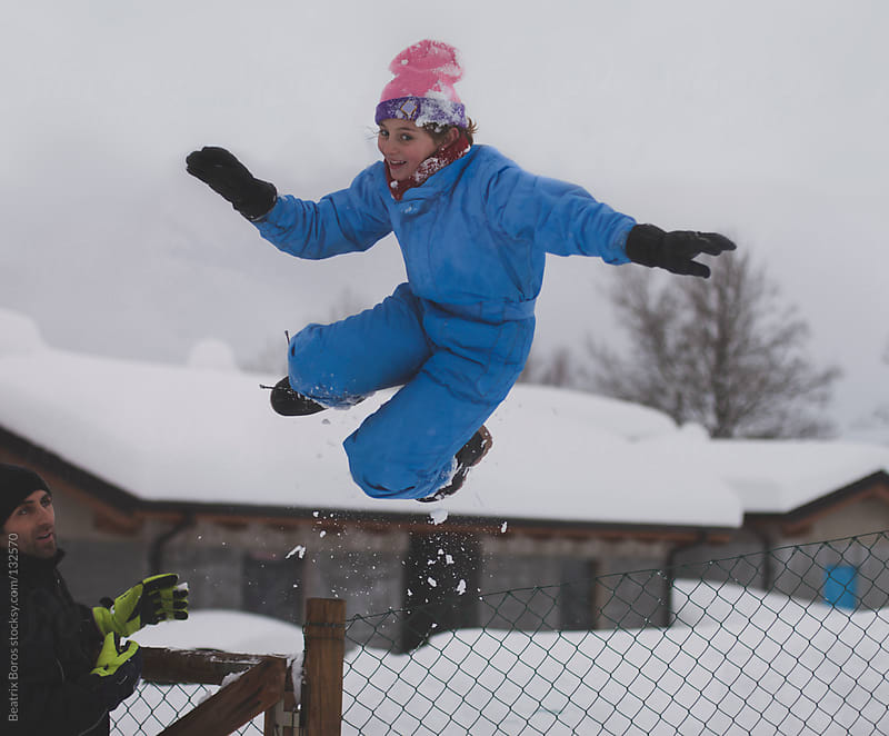 Girl jumping in the snow while father is watching her by Beatrix Boros for Stocksy United