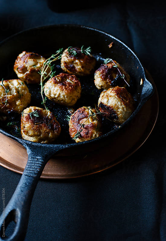 Meatballs in a cast iron skillet.  by Darren Muir for Stocksy United