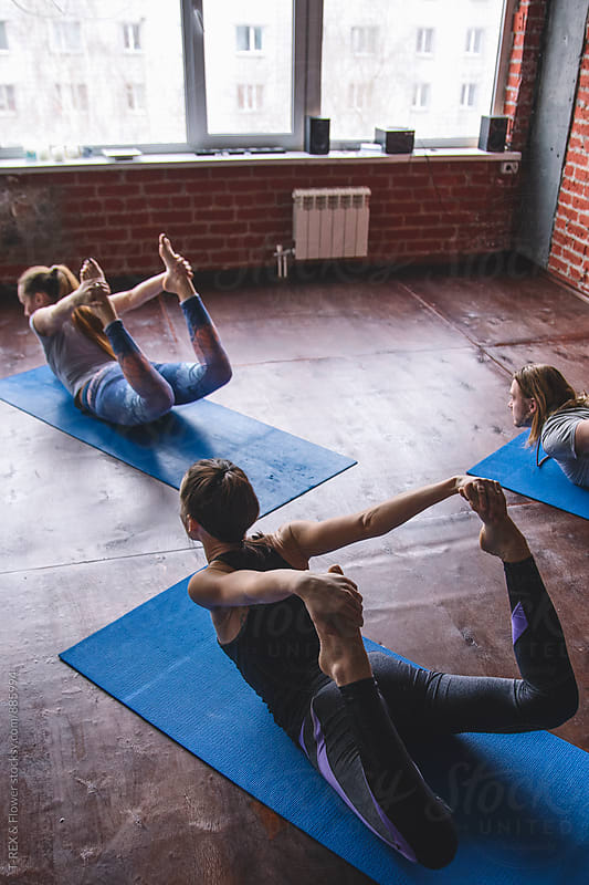 Three people practicing bow pose by Danil Nevsky for Stocksy United