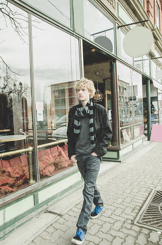 Young Man Walking Down City Street by Tomas Kraus for Stocksy United
